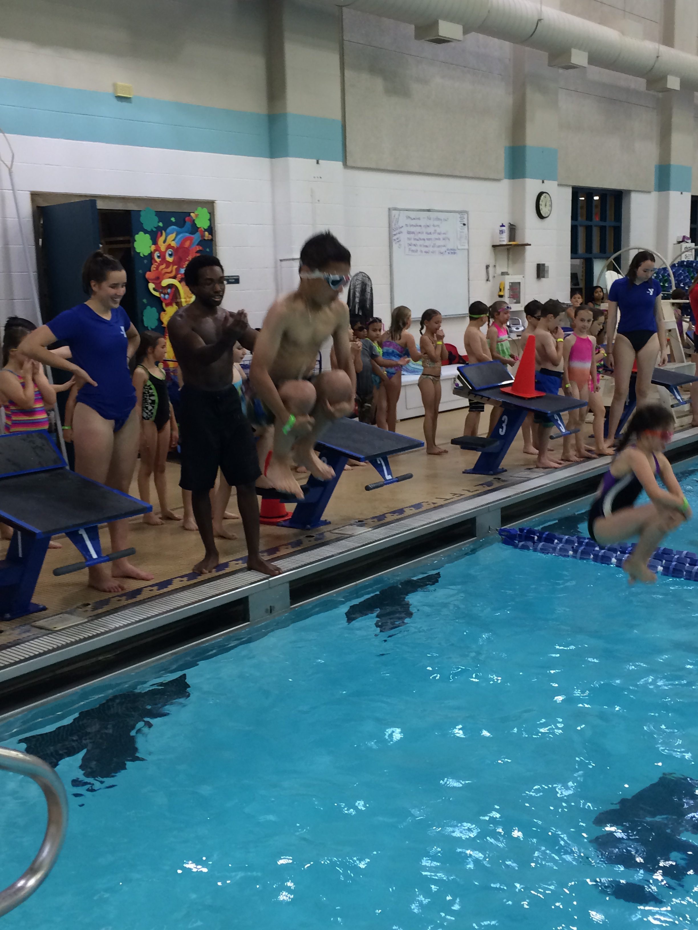 Students jumping into the pool