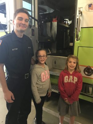 Students posing with a firefighter