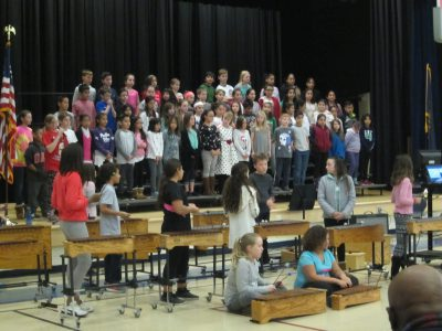 Choir singing , students playing xylophones
