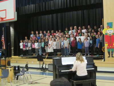 Choir singing with Mrs. Urglavitch, music teacher, playing the piano