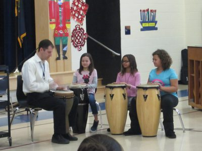 Students and Mr. Green, music teacher, playing drums
