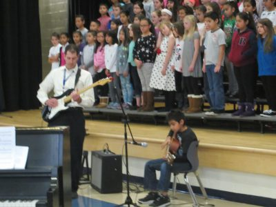 Mr. Green, music teacher, and student playing guitars