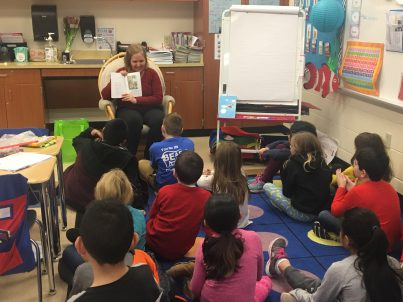 Adult reading to second grade students