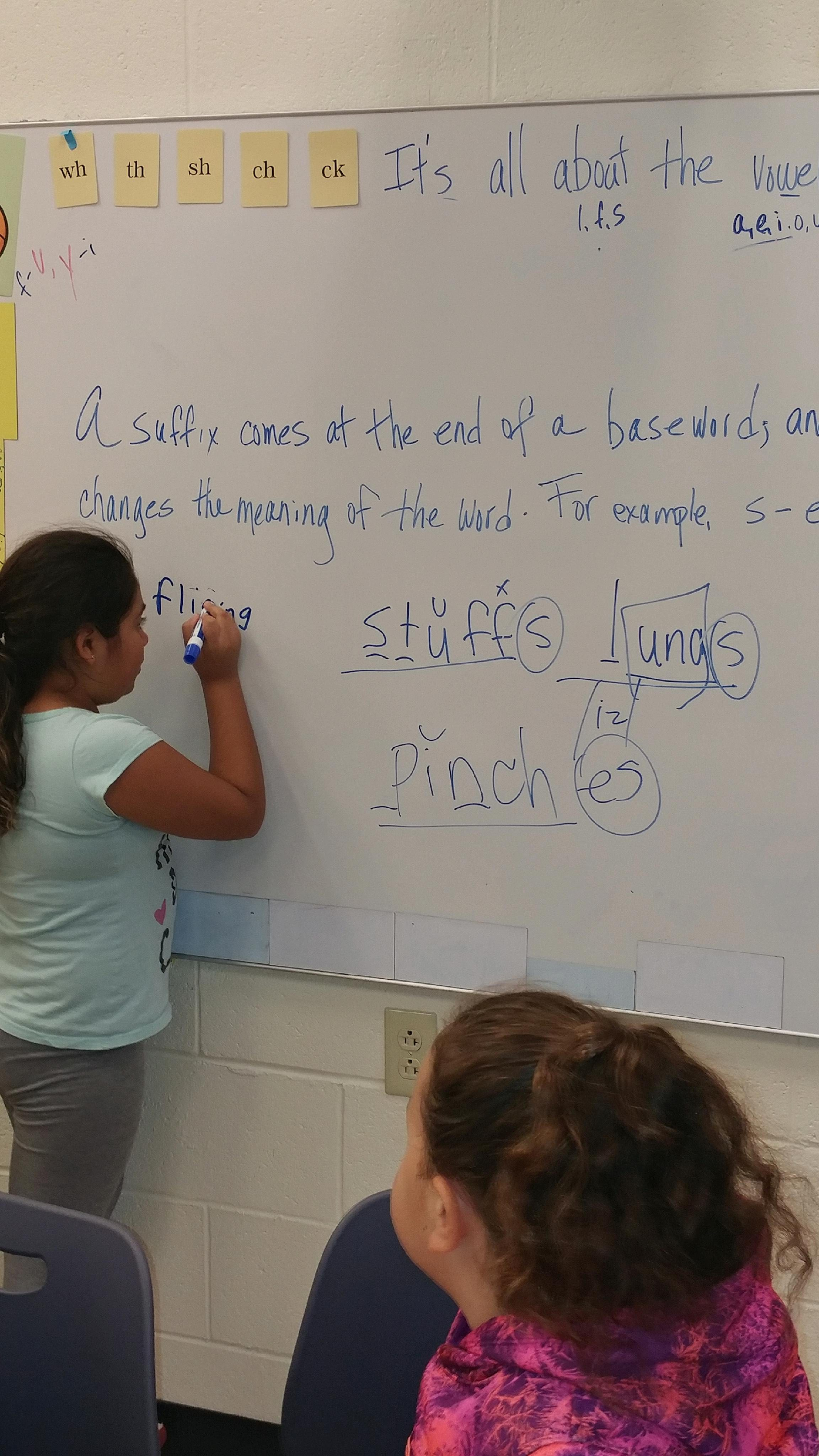 student writing on white board