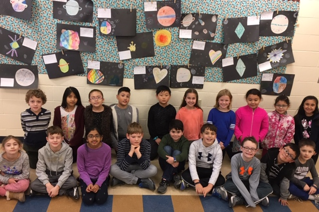 students in front of planet bulletin board
