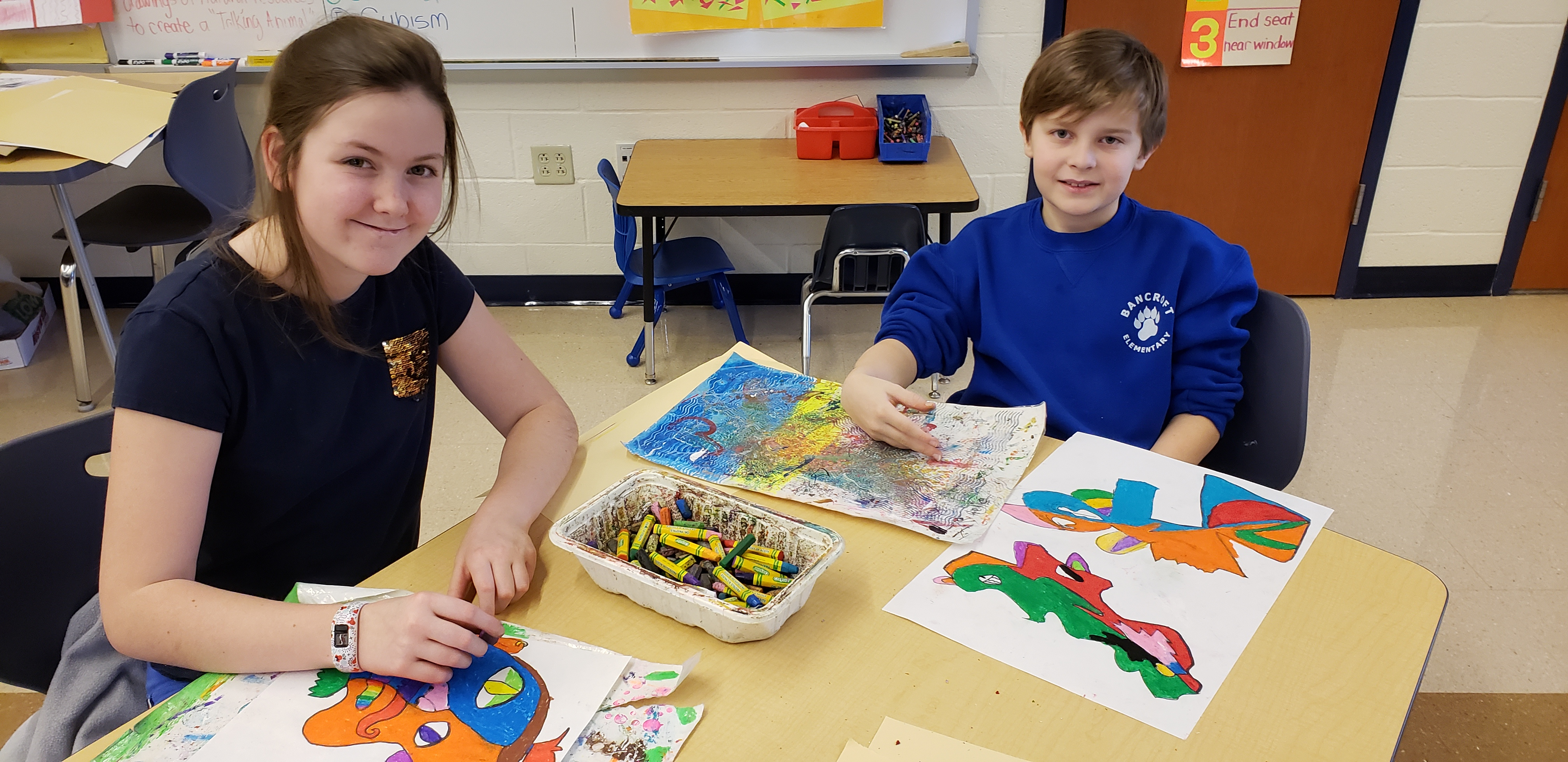two students coloring and drawing