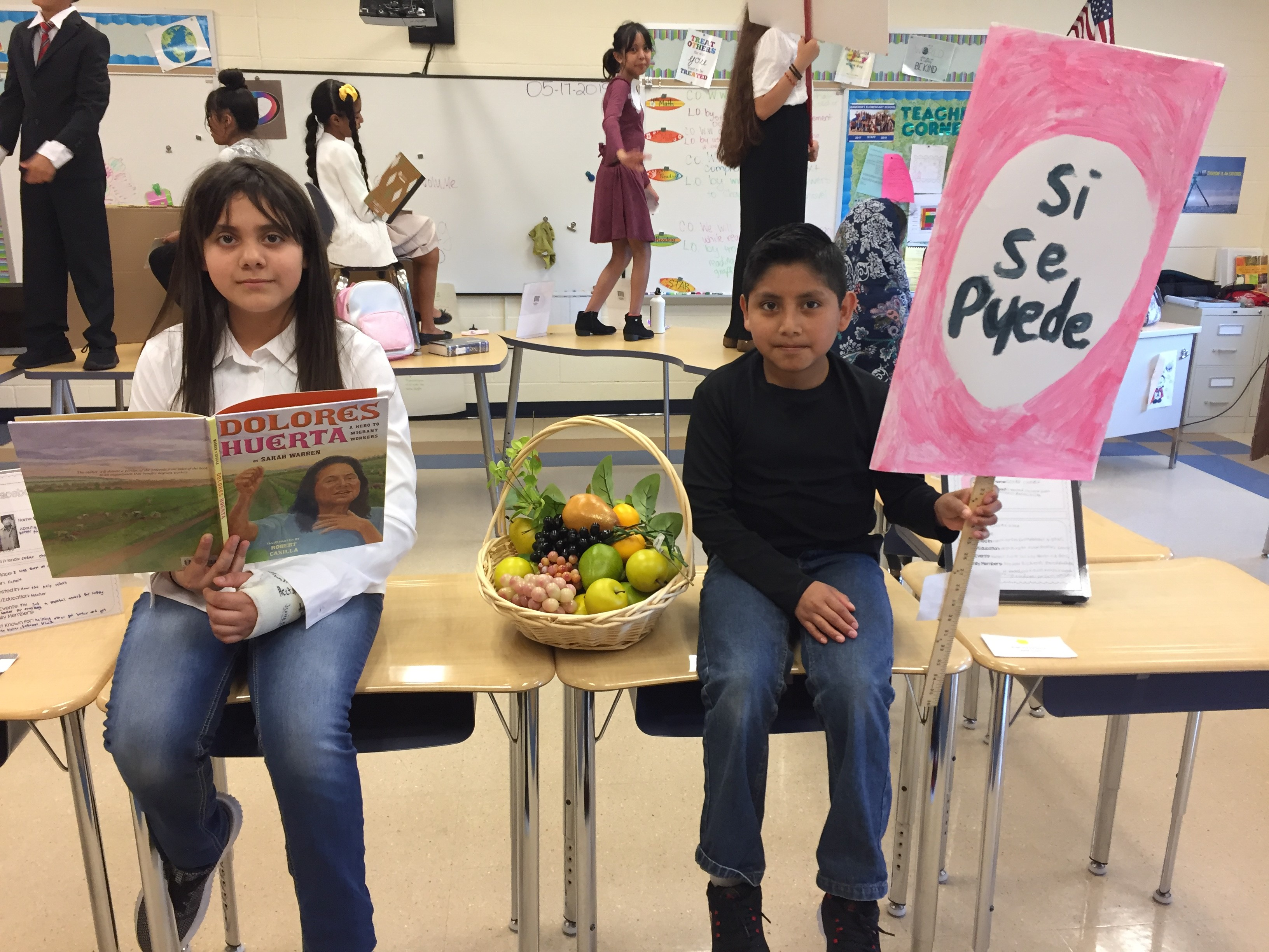 students sitting on desks holding a book and sign