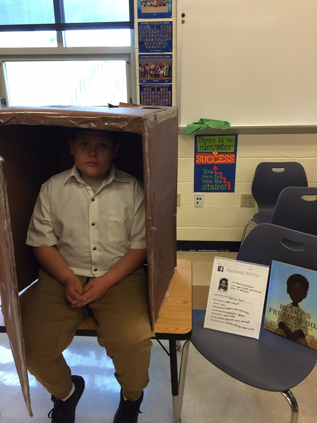 student sitting on desk with box