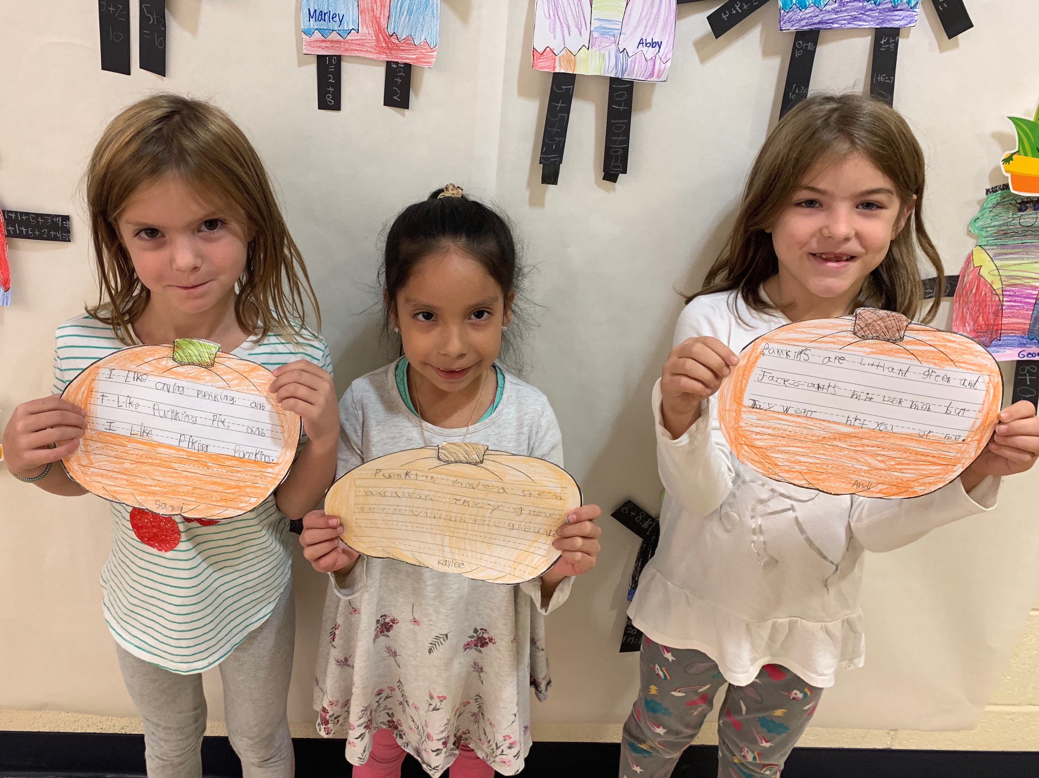 students holding paper pumpkins with writing
