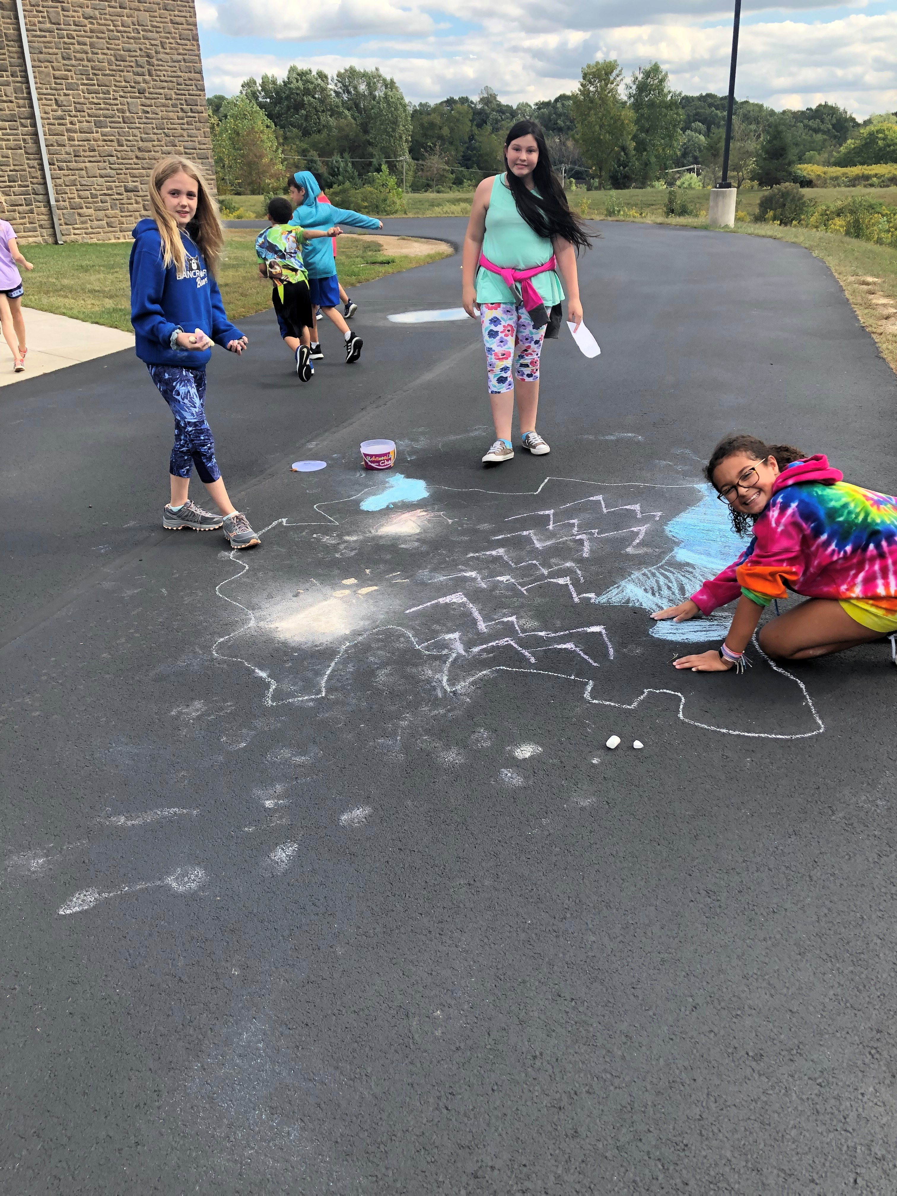 students drawing on sidewalk